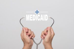 Hands holding a stethoscope with the word Medicaid between the earpieces.