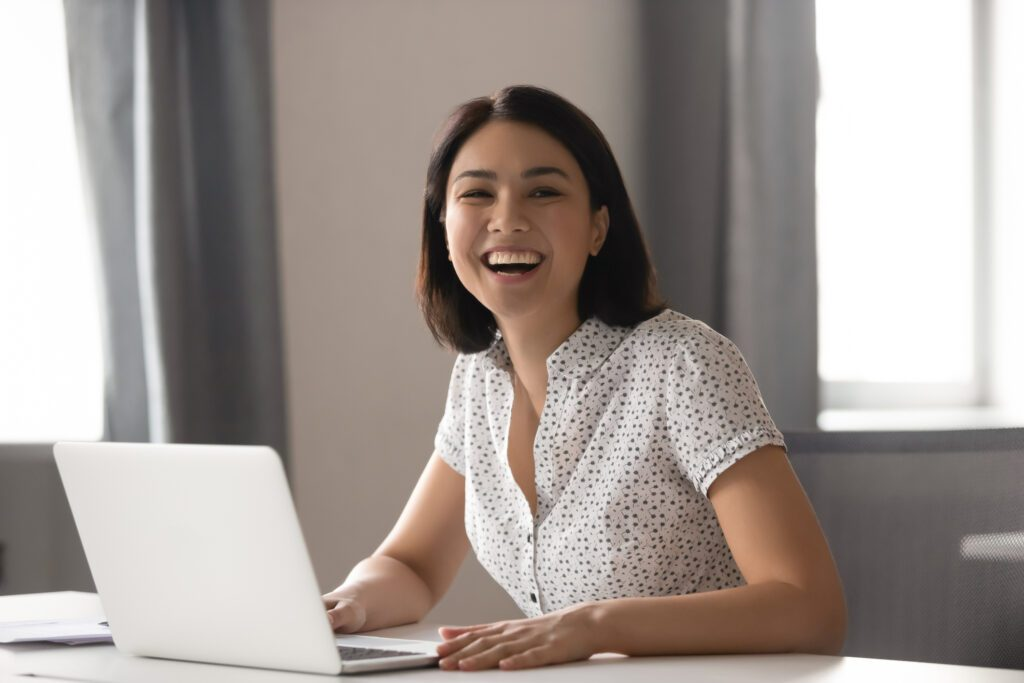 A medical billing professional smiling at her computer.