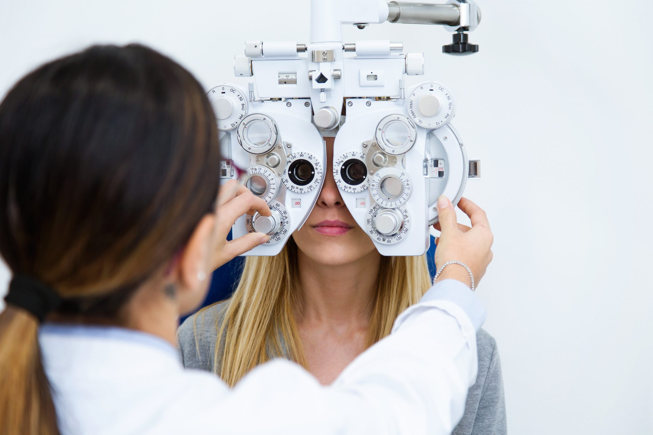 An optometrist performing a routine eye exam on her patient.
