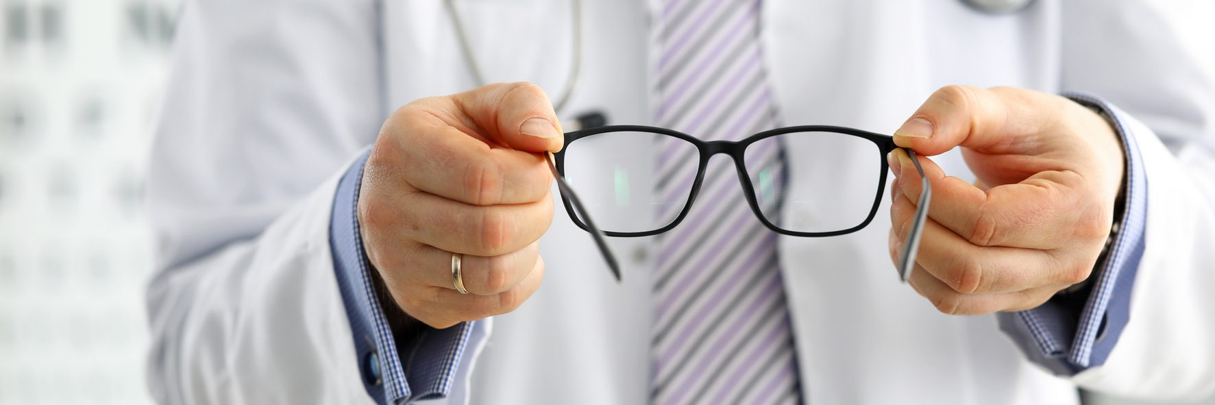 Optician offering glasses to a patient.